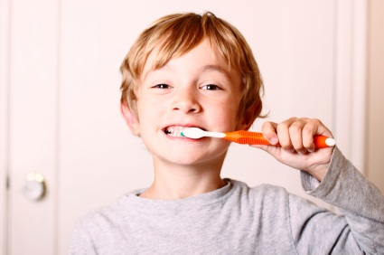A boy brushing his teeth to hard causing damage to his gums.